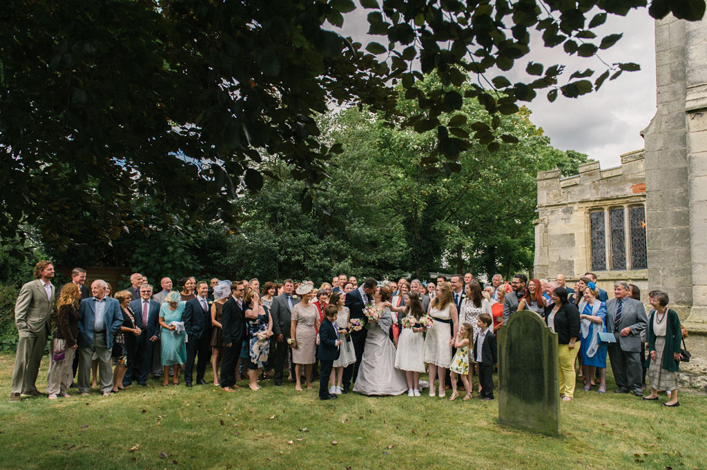 Brode and groom with wedding guests outside St John the Baptist's church in Misson
