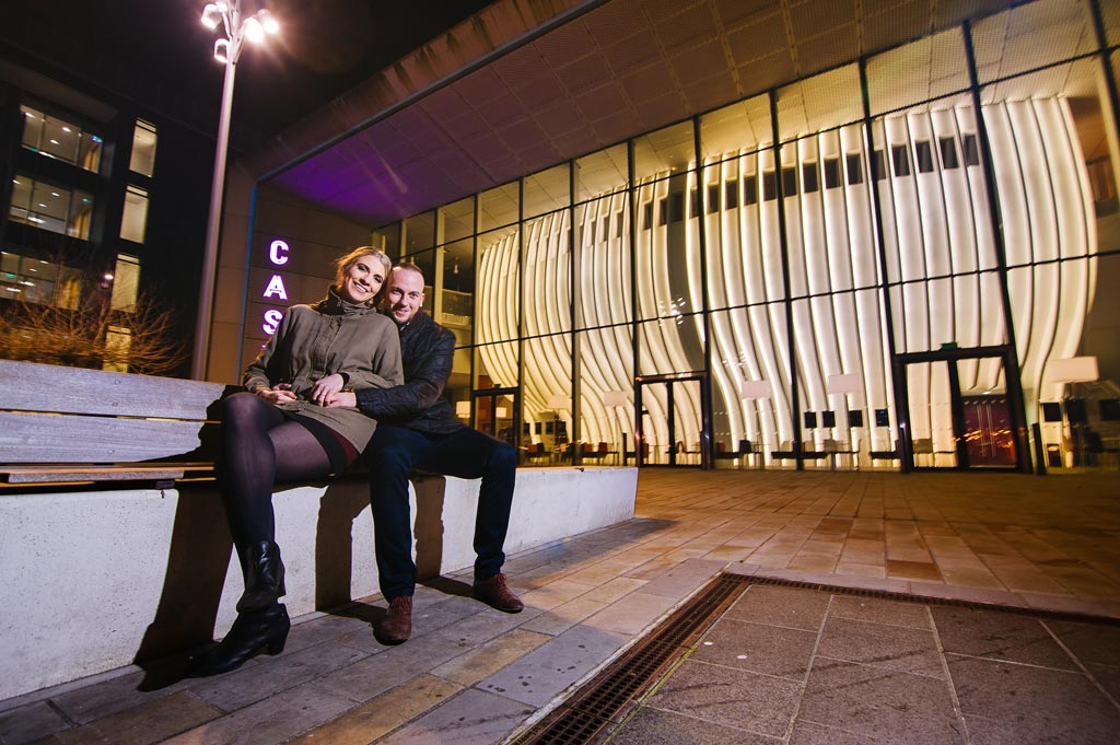 Newly engaged couple sitting on a bench outside Cast theatre in Doncaster, South Yorkshire