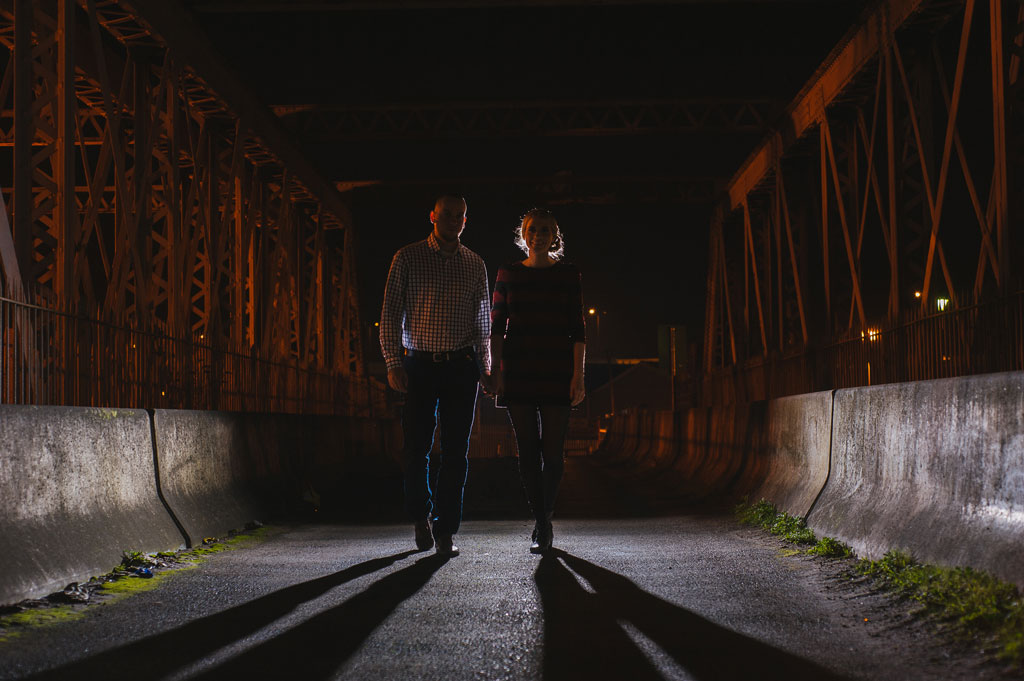 Engaged couple backlit walking over a bridge in Doncaster