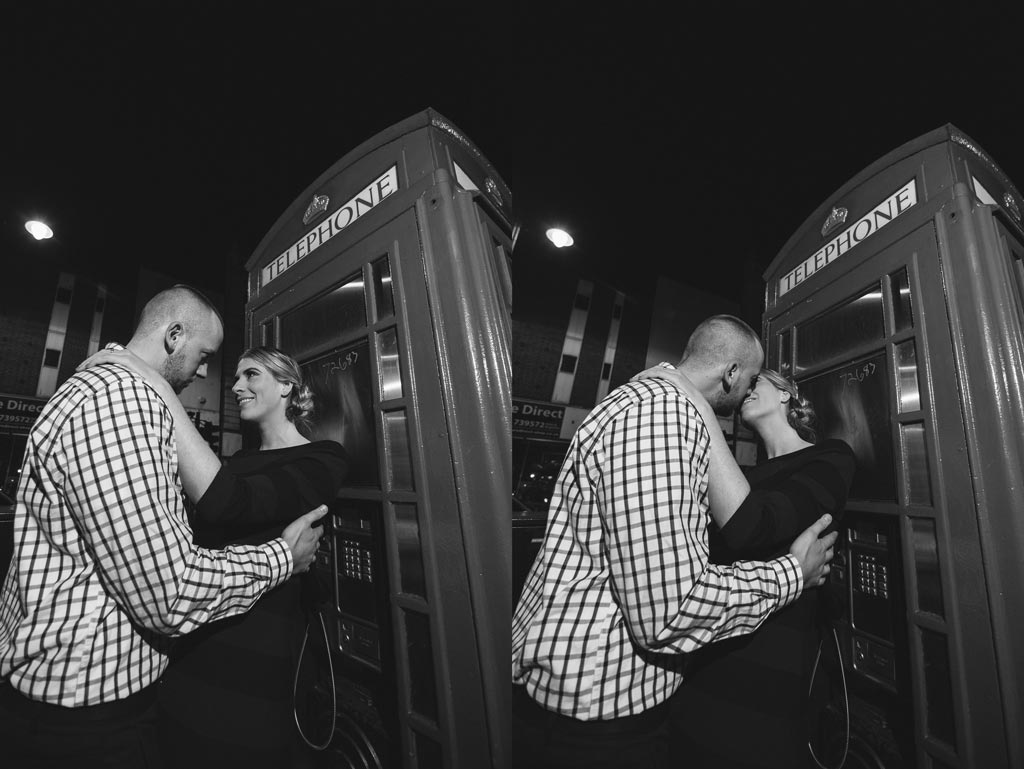 Newly engaged couple against a red telephone booth