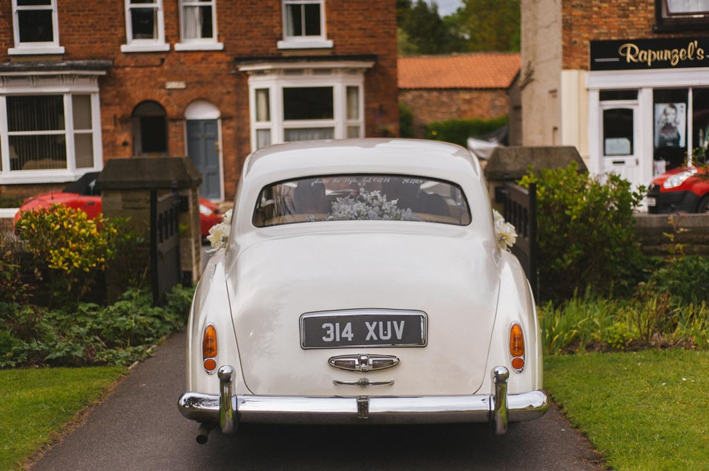 Wedding classic car leaving with bride and groom