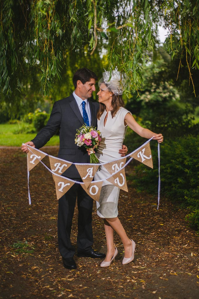 Maried couple holding thank you bunting