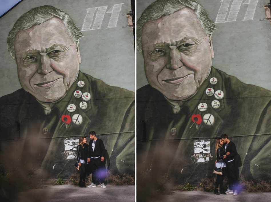 A couple having their engagement photo taken with a mural of David Attenborough in the Sheffield City Centre