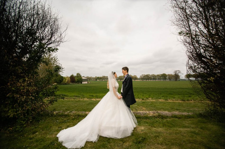 Bride and groom in a field outside The Stables