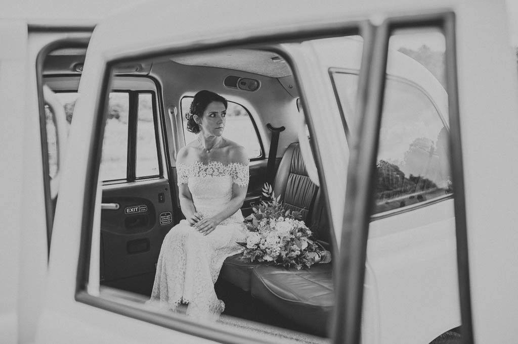 Bride arriving in a white London cab at Hazel Gap wedding barn