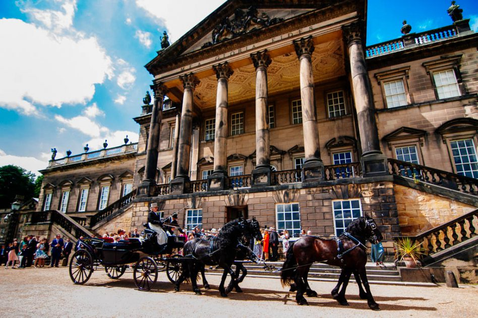 Bride arriving in a horse drawn carriage at Wentworth Woodhouse