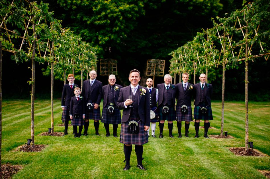 Groom and best men in Scottish kilts photographed outside Hazel Gap Barn