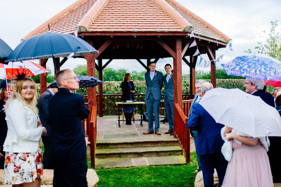 Groom and best man waiting during outdoor wedding ceremony
