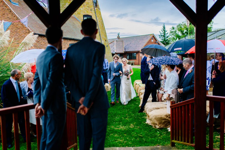 Bride walking down aisle during outdoor wedding ceremony