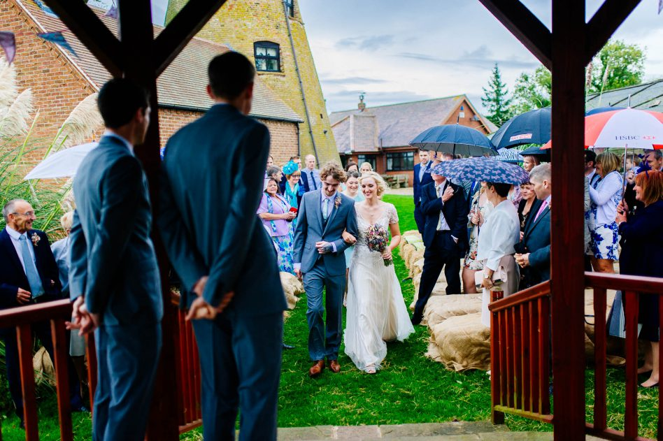 Bride walking down aisle during an outdoor ceremony at Fishlake Mill