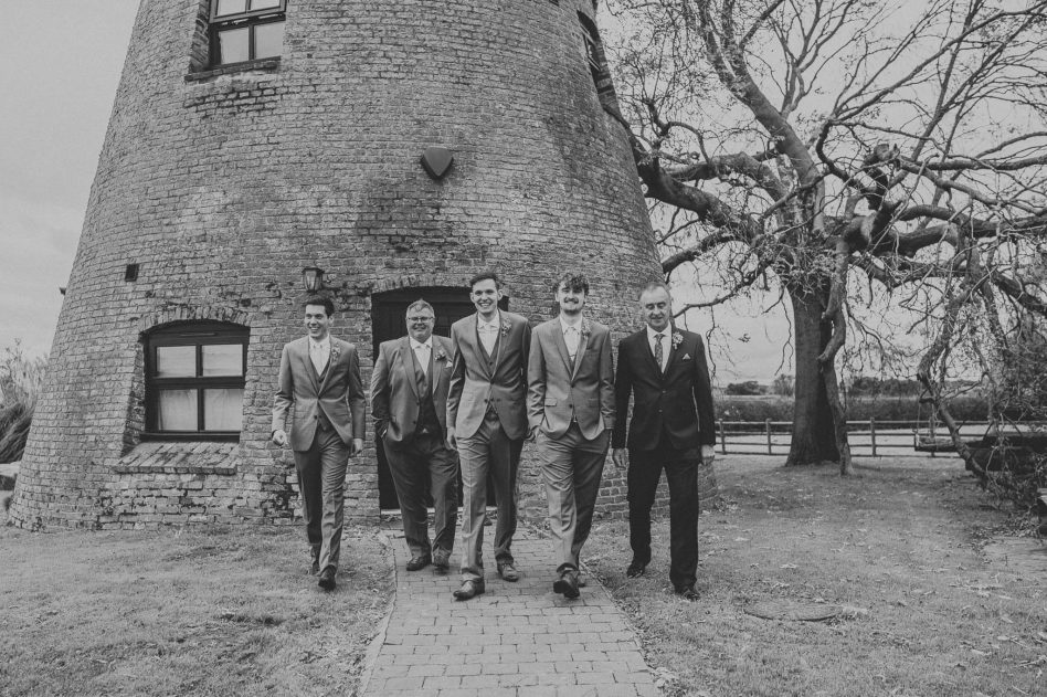 Groom with groomsmen walking away from Fishlake Mill