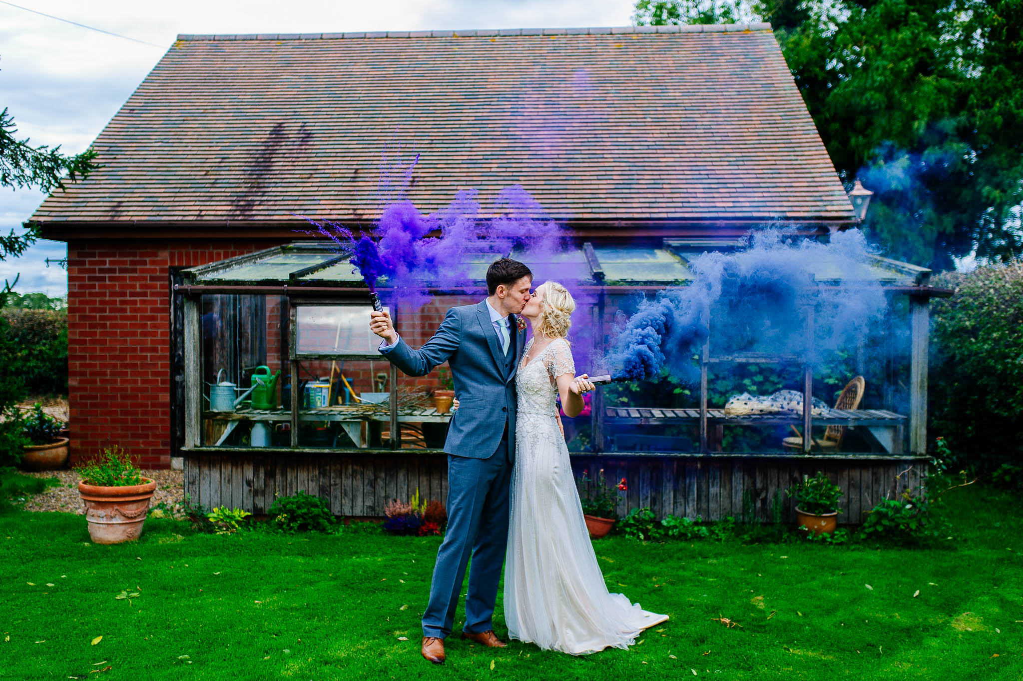 Married couple holding smoke bombs at Fishlake Mill