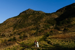 Bride and groom climbing Arthur's Seat in Edinburgh
