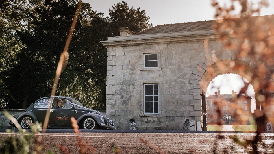Bride in a vintage VW Beatle outside Cusworth Hall wedding venue