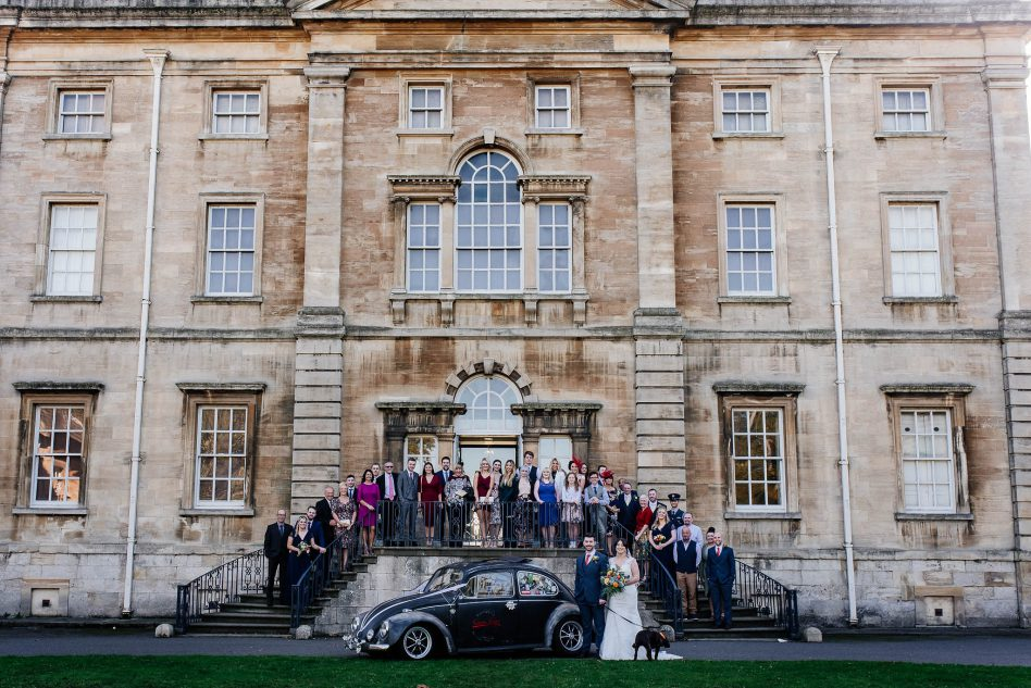 A group wedding photo on a staircase at Cusworth Hall