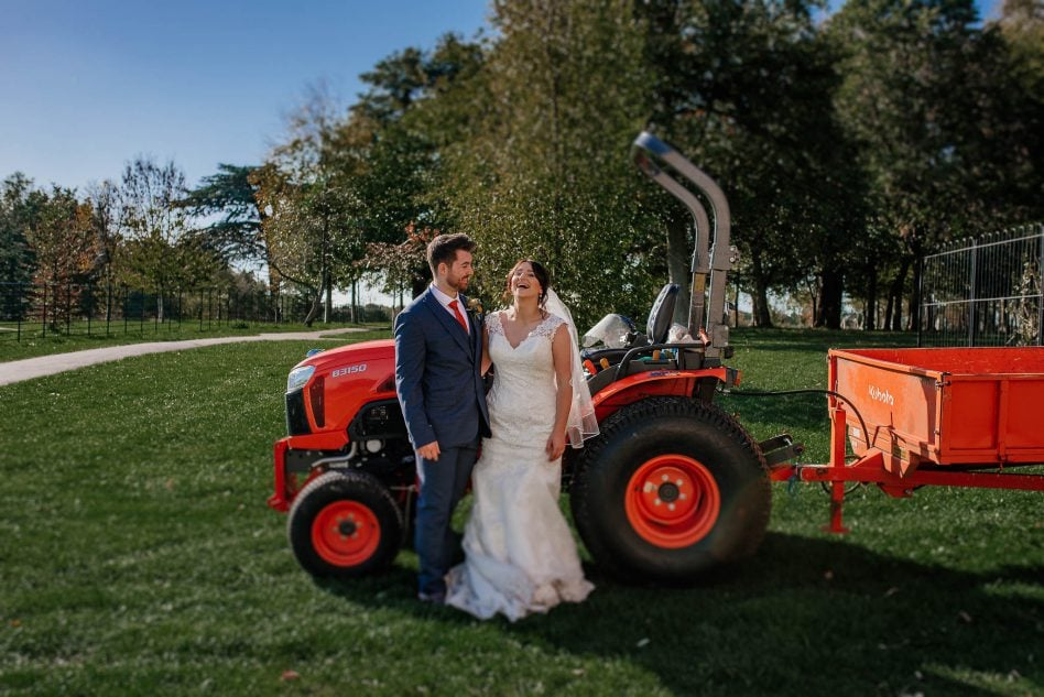 Bride and groom posing with a tractor at Cusworth Hall