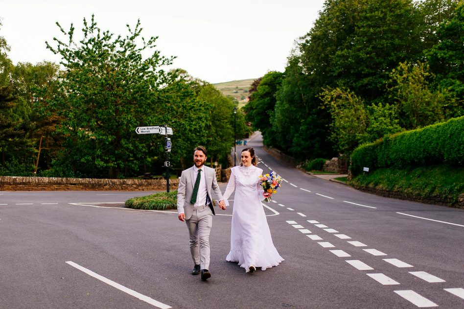 Newlyweds walking in the Peak District on their wedding day