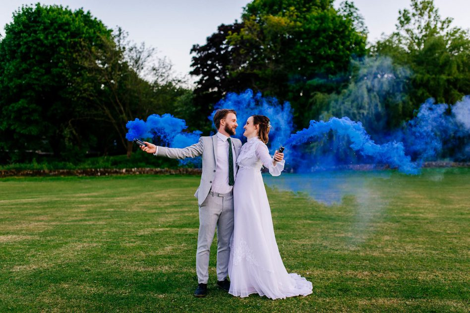 Bride and groom holding smoke bombs