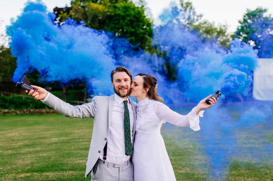 Bride and groom with blue smoke bombs