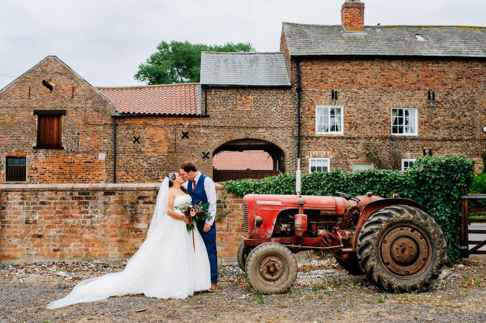 Bride and groom with a tractor outside The Normans Wedding Venue