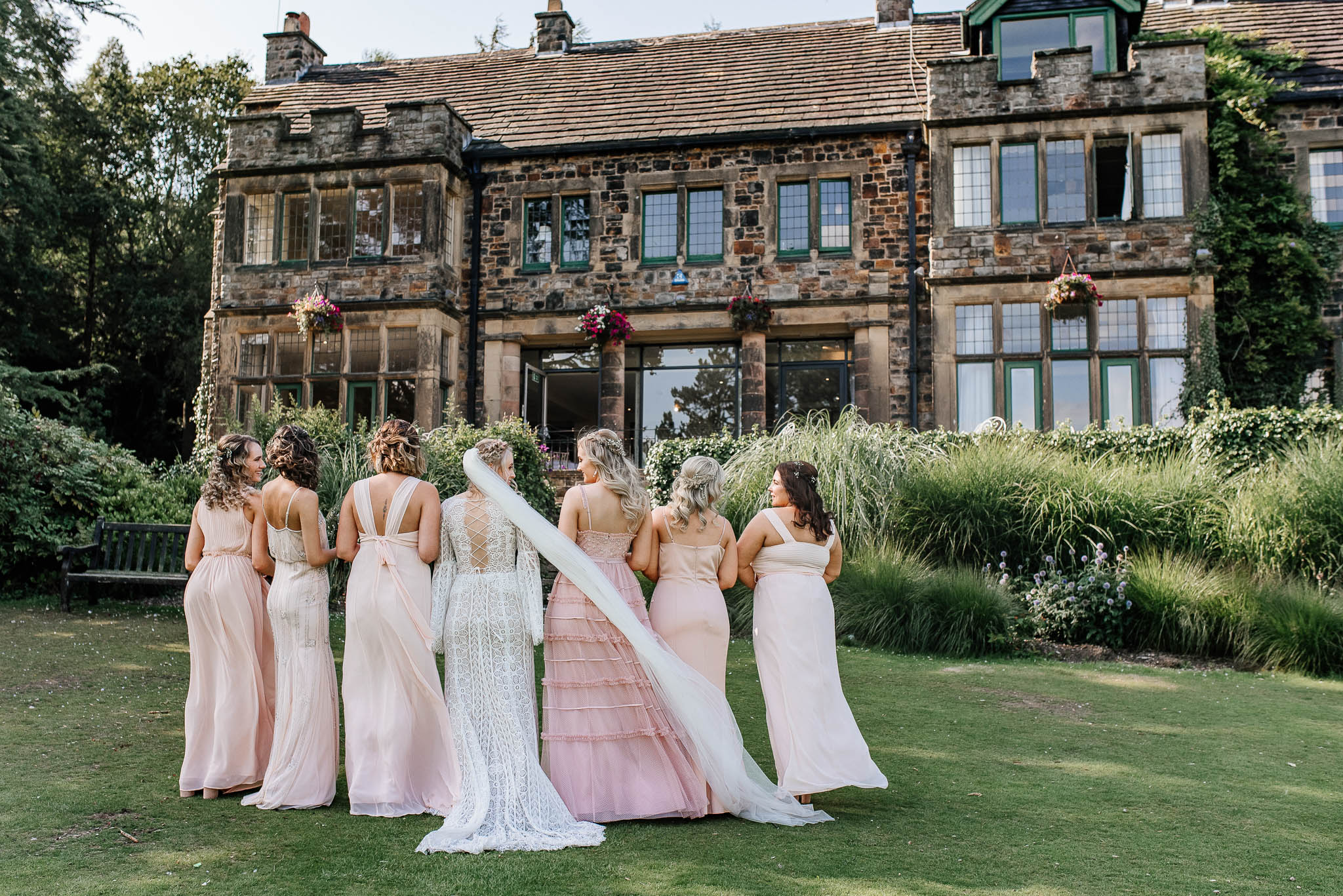 Bride and bridesmaids standing outside Whirlowbrook hall wedding venue
