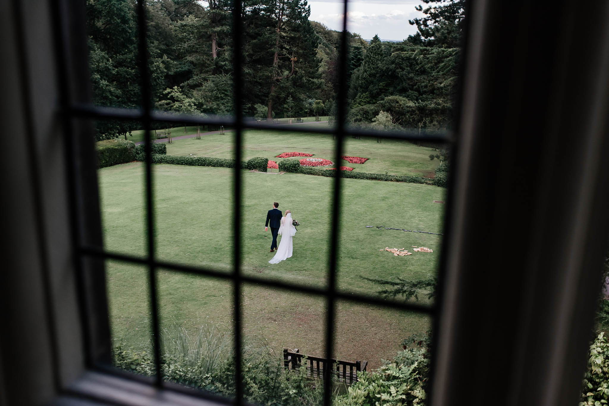 Bride and groom walking in garden at whirlowbrook Hall