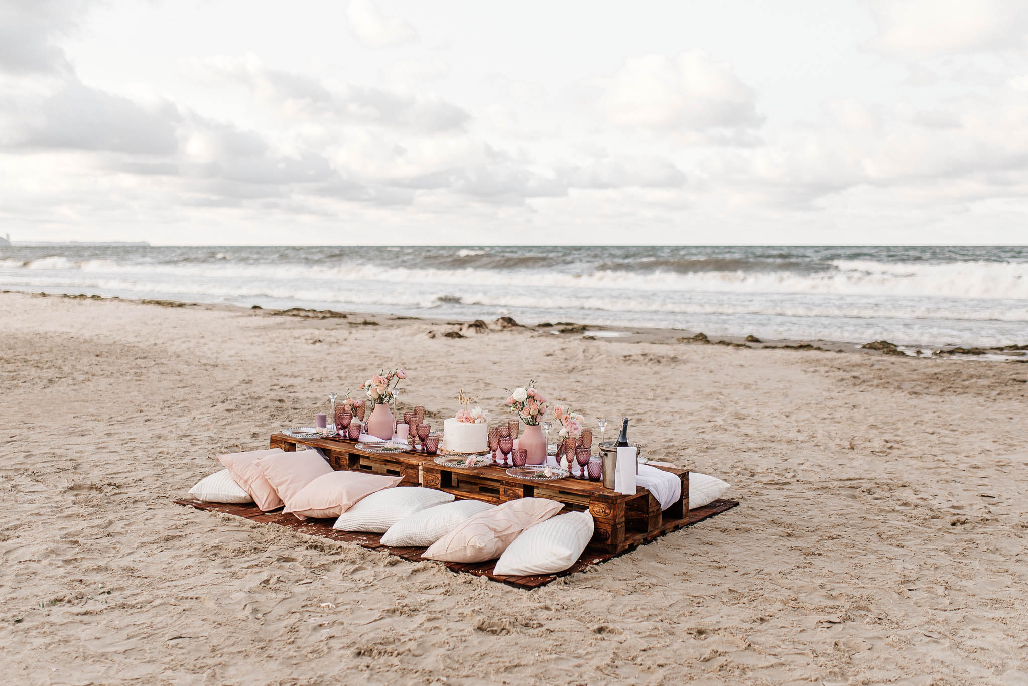 A beach wedding setup using wooden pallets